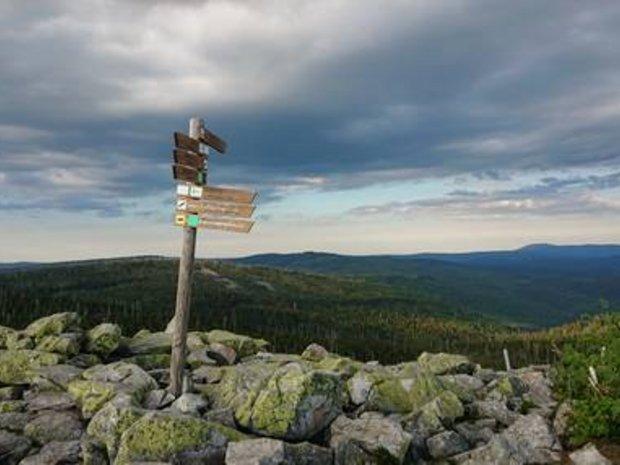 Bergiges Panorama im Vordergrund ein Wegweiserschild
