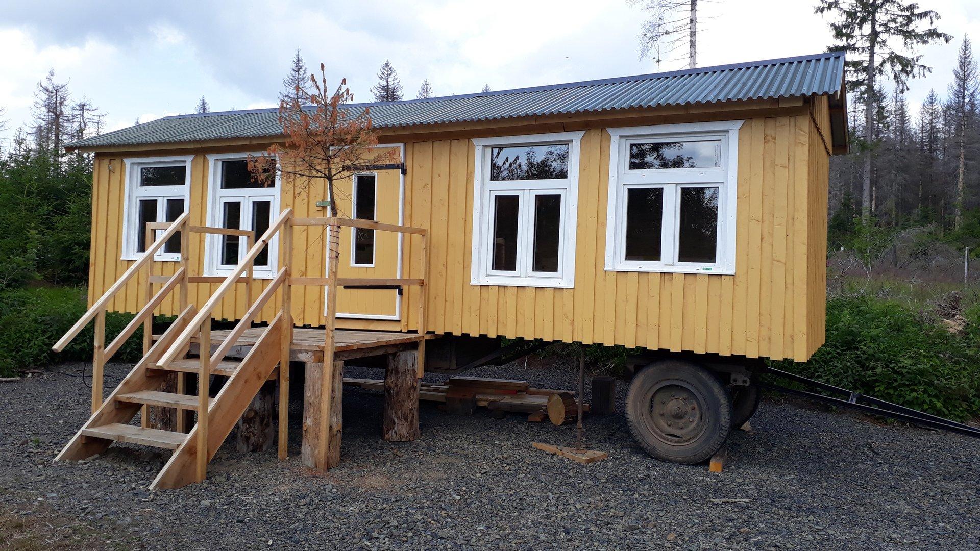 Das Waldlabor: ein gelber Holz-Bauwagen mit großen Fenstern auf einer Lichtung