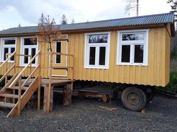Das Waldlabor: Ein gelber Bauwagen mit großen Fenstern auf einer Waldlichtung