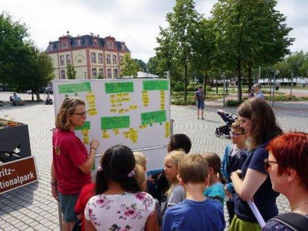Schulklasse lässt sich ein Plakat im Freien erklären