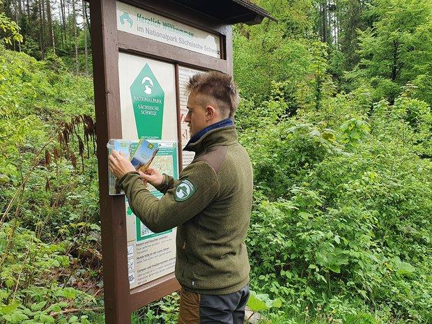 Ein Flyerhalter wird an einem Eingang des Nationalparks angebracht