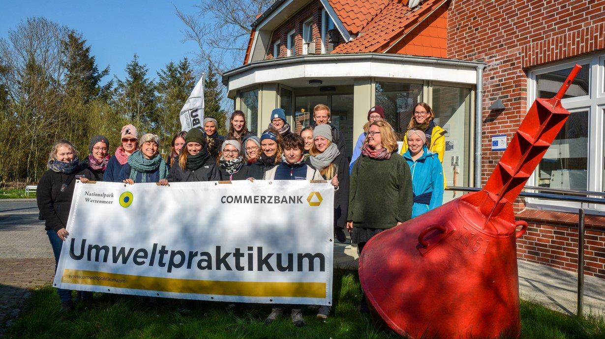 """Bild von Gruppe mit Banner mit der Aufschrift """"Umweltpraktikum"""""""
