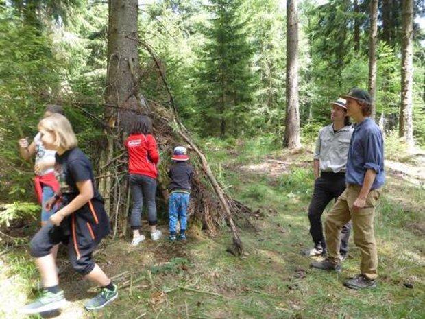 Kinder bauen Unterschlupf mit Ästen an einem Baum