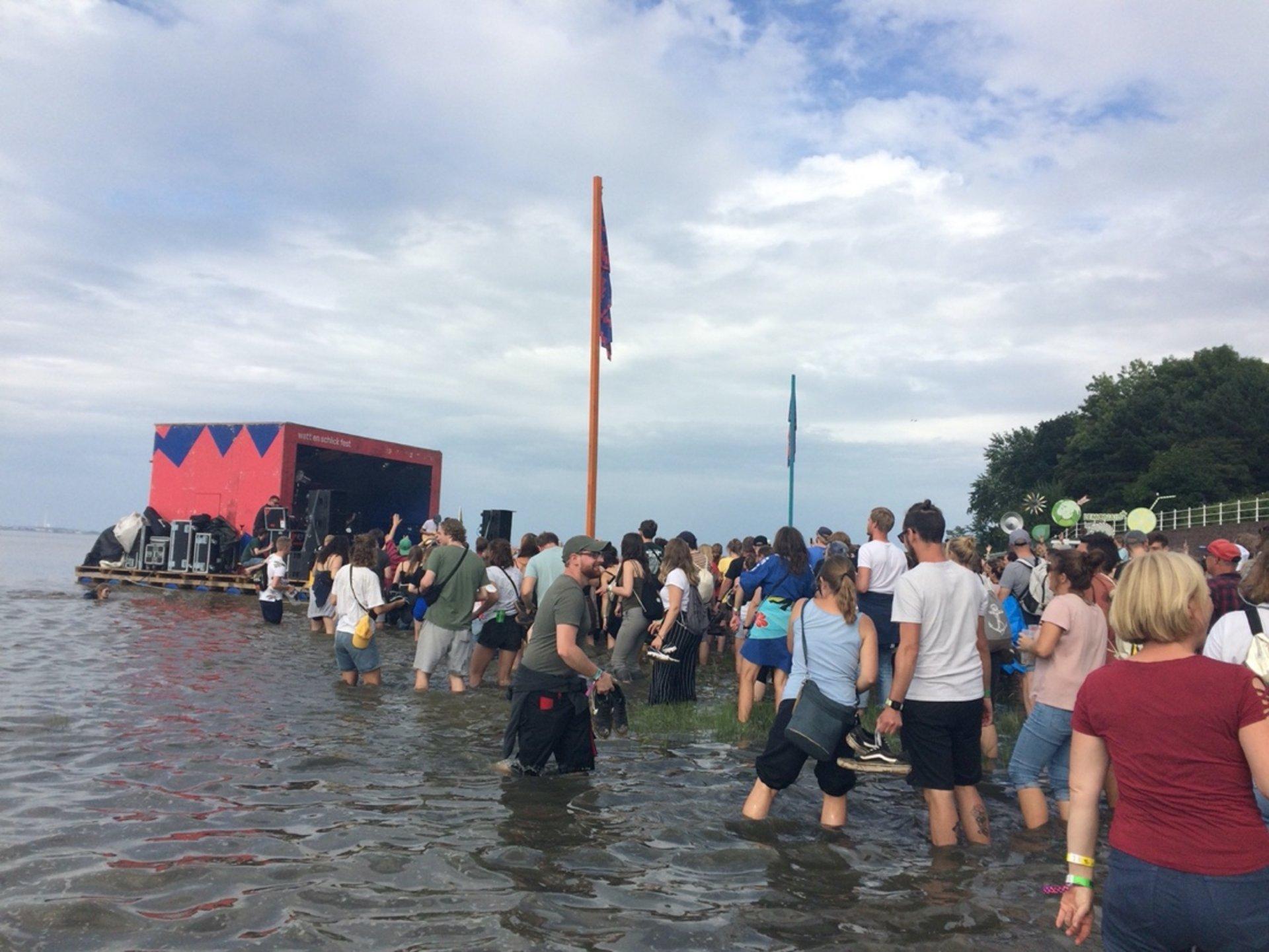 Eine Gruppe Menschen feiert vor einer Bühne, die ins Wasser gebaut ist
